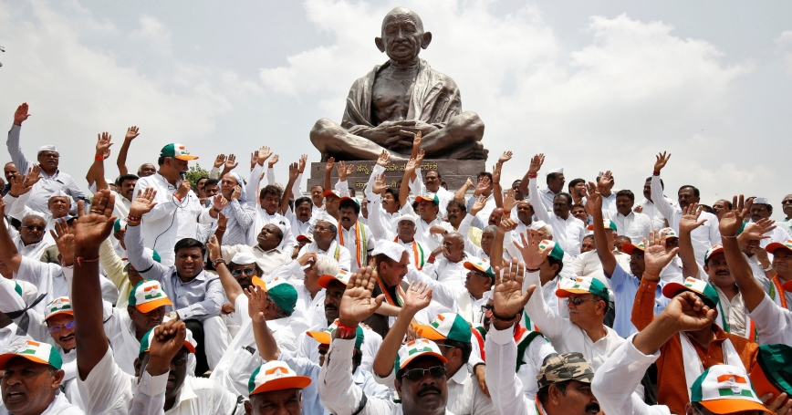 Indian man hold their hands up while facing their backs towards a Buddha statue