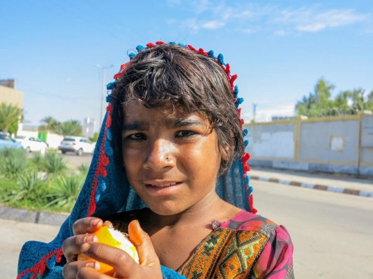 This is a photo of a young Baluchi girl holding an orange.